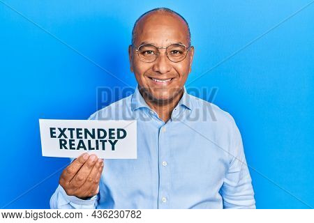 Middle age latin man holding paper with extended reality message looking positive and happy standing and smiling with a confident smile showing teeth