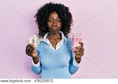 Young african american woman eating doughnut and drinking coffee skeptic and nervous, frowning upset because of problem. negative person.
