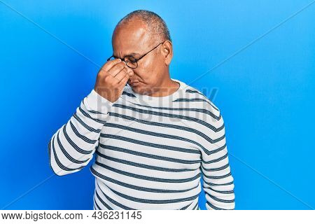 Middle age latin man wearing casual clothes and glasses tired rubbing nose and eyes feeling fatigue and headache. stress and frustration concept.