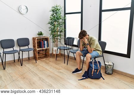 Young arab man desperate with hands on head sitting on the chair at waiting room