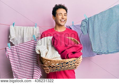 Handsome hispanic man doing laundry holding wicker basket winking looking at the camera with sexy expression, cheerful and happy face.