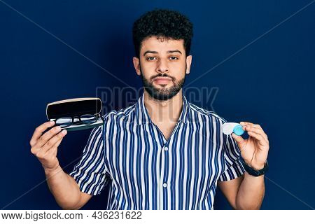 Young arab man with beard holding glasses and contact lenses relaxed with serious expression on face. simple and natural looking at the camera.