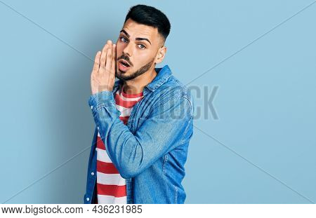 Young hispanic man with beard wearing casual denim jacket hand on mouth telling secret rumor, whispering malicious talk conversation