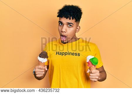 Young african american man wearing t shirt with happiness word message holding ice cream in shock face, looking skeptical and sarcastic, surprised with open mouth
