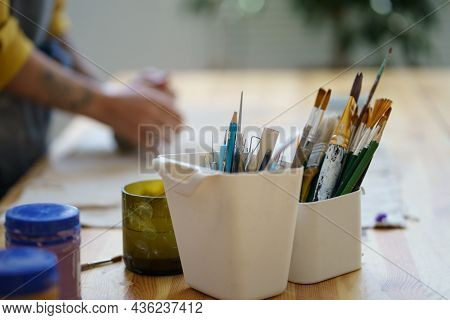 Work Table Of Pottery Decorator With Bowls Of Different Paintbrushes For Coloring Clay Crockery With
