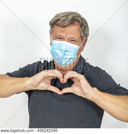 Portrait Of Man Wearing A Mask For Corona Protection And Showing A Heart