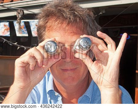 Funny Man Is Joking And Putting Salt Spender As Eyes In Front Of His Eyes