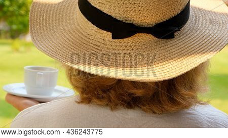 Happy Woman In A Straw Hat Holds A Cup Of Hot Drink And Drinks Coffee, Sitting In The Morning On A S
