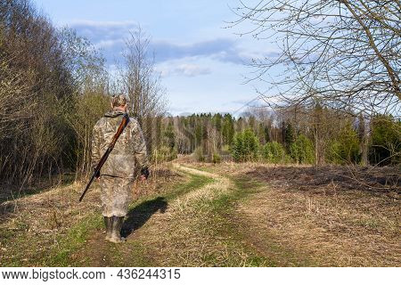 A Hunter Walks Along The Road In The Spring Forest. He's Got A Shotgun On His Back. Light From The L