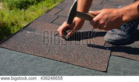 A Close-up Of Asphalt Shingles Installation On The Roof Edge. A Roofer Is Nailing Asphalt Shingles T