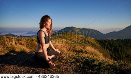 Attractive Young Woman In Sportswear Sitting On Grassy Hill In Lotus Position And Doing Gyan Mudra H