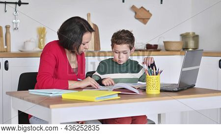 Female Private Tutor Helping Young Student With Homework At Desk In Bright Childs Room. Mother Helps