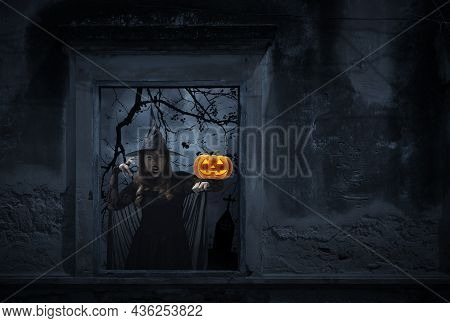 Halloween Witch With Pumpkin Monster Head Standing In Old Damaged Window With Wall Over Cross, Churc
