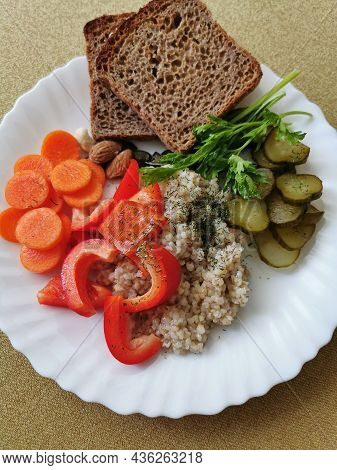 Barley groats with red pepper, carrots, pickled cucumber, wholemeal bread, parsley and nuts