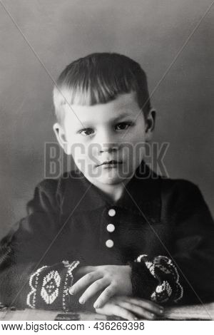 Retro Portrait Of Soviet Boy Sitting With Folded Hands. Vintage Black And White Paper Photo. Early 1