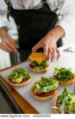 Technique For Making Cheeseburgers At Home. The Chef Assembles The Finished Dish.