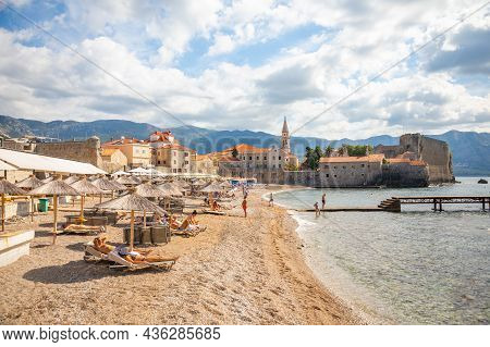 Budva, Montenegro - September 18, 2021: Beach Of Old Town Budva. Ancient Walls And Tiled Roof Of Old