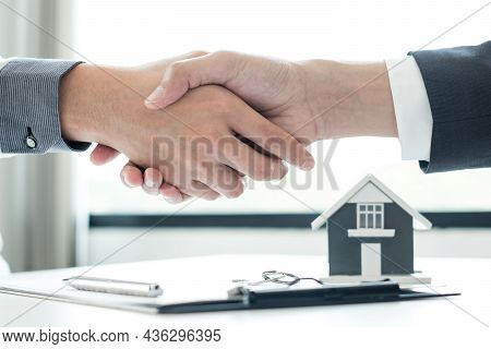 Businessmen And Brokers' Real Estate Agents Shake Hands After Completing Negotiations To Buy Houses