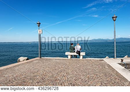 Lazise, Italy - May 26, 2021: Two People Relax Sitting On A Bench On The Coast Of Lake Garda. Port O