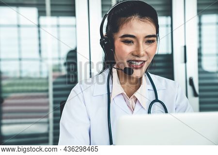 Doctor Wearing Headset Talking Actively On Video Call In Hospital Or Clinic . Concept Of Telehealth