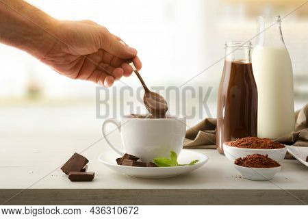 Hand Stirring Freshly Prepared Hot Chocolate On Kitchen Bench With Portions And Powdered Chocolate A