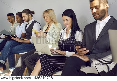 Multiracial People Using Laptops And Cellphones While Waiting In Line For Job Interview