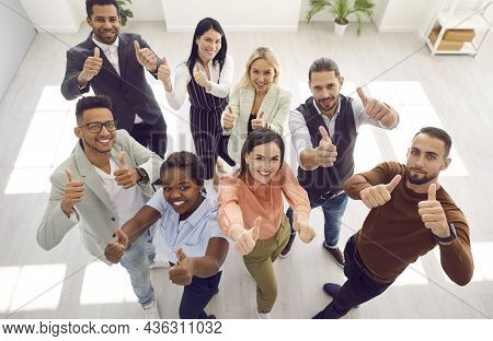 Diverse Team Of Happy Business People Standing In Office, Looking Up, Smiling And Giving Thumbs Up