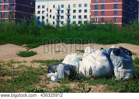Pile Of Garbage Packages On A Ground Against On Blurred Multi Apartment House. Waste Plastic. Garbag