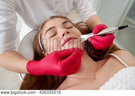 Cosmetologist Making Hardware Cleaning Of The Face Of Beautiful Young Patient. Concept Skin Cleansin