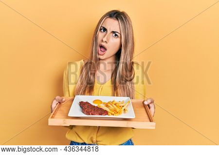 Beautiful hispanic woman holding tray with meat loaf and fried egg in shock face, looking skeptical and sarcastic, surprised with open mouth