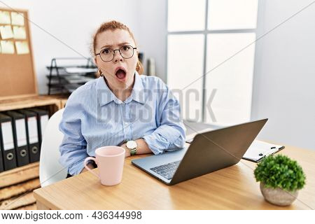 Young redhead woman working at the office using computer laptop in shock face, looking skeptical and sarcastic, surprised with open mouth