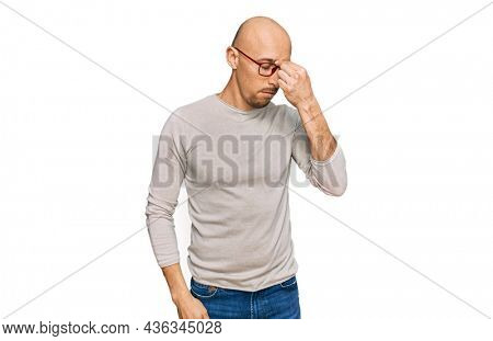 Bald man with beard wearing casual clothes and glasses tired rubbing nose and eyes feeling fatigue and headache. stress and frustration concept.