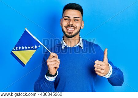 Young hispanic man with beard holding bosnia herzegovina flag smiling happy and positive, thumb up doing excellent and approval sign