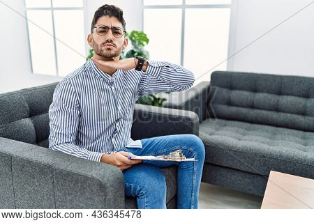 Young psychologist man at consultation office cutting throat with hand as knife, threaten aggression with furious violence
