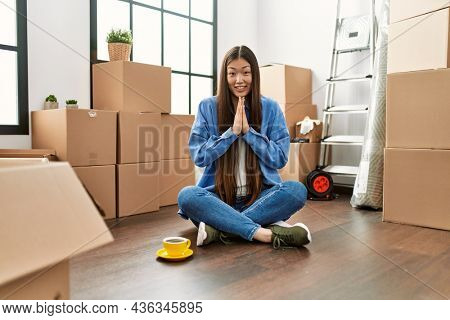 Young chinese girl sitting on the floor at new home praying with hands together asking for forgiveness smiling confident.