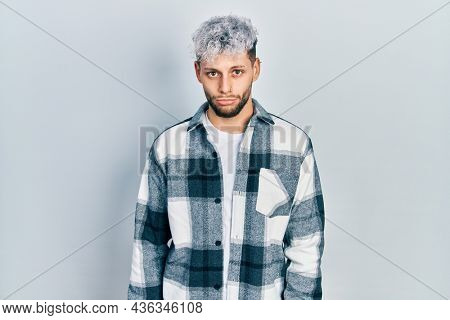 Young hispanic man with modern dyed hair wearing casual shirt depressed and worry for distress, crying angry and afraid. sad expression.