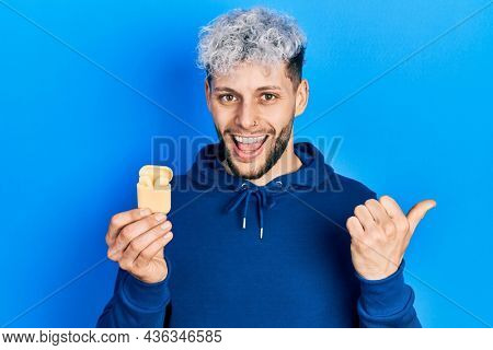 Young hispanic man with modern dyed hair holding wireless earphones pointing thumb up to the side smiling happy with open mouth
