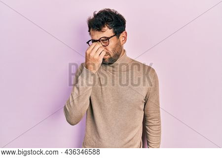 Handsome man with beard wearing turtleneck sweater and glasses tired rubbing nose and eyes feeling fatigue and headache. stress and frustration concept.