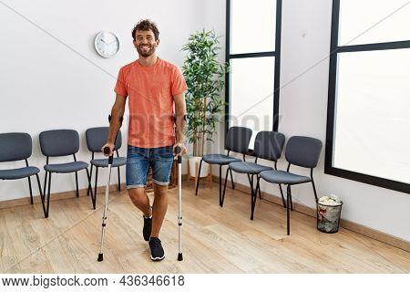 Young hispanic man walking using crutches at clinic waiting room.