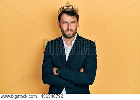 Handsome man with beard wearing business suit with arms crossed gesture and king crown skeptic and nervous, frowning upset because of problem. negative person.