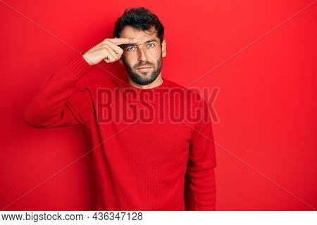 Handsome man with beard wearing casual red sweater pointing unhappy to pimple on forehead, ugly infection of blackhead. acne and skin problem