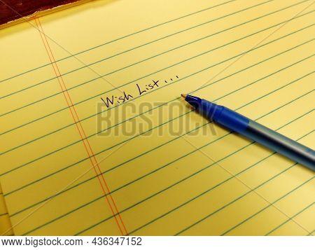 Wish list written in blue ink on notebook with blue pen