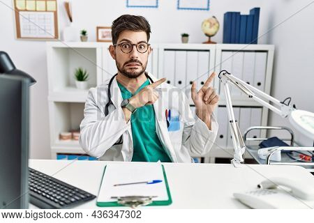 Young man with beard wearing doctor uniform and stethoscope at the clinic pointing aside worried and nervous with both hands, concerned and surprised expression