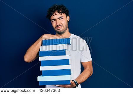 Young hispanic man holding a pile of books in shock face, looking skeptical and sarcastic, surprised with open mouth