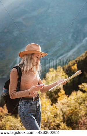 Wanderlust And Travel Concept. Stylish Traveler Girl In Hat Looking At Map, Exploring Woods.