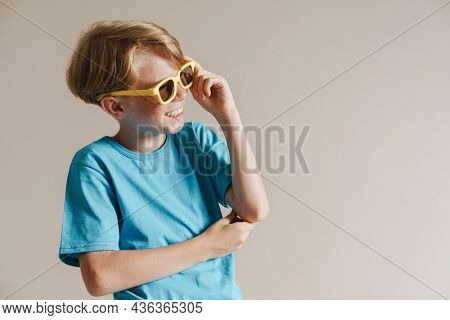 Portrait of a happy smiling casual preteen boy in t-shirt standing over isolated gray wall background looking aside