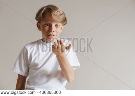Portrait of a shocked casual preteen boy in t-shirt standing over isolated gray wall background holding copy space on his palm