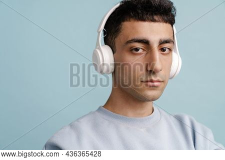 Young middle eastern man in headphones posing at camera isolated over blue background