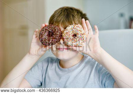 Happy Preteen School Boy Eating Sweet Donut Indoor. Blond Child In Domestic Kitchen Or In School Can