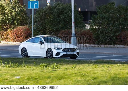 Moscow; Russia - October 14; 2021: White Mercedes E-class Coupe Is Driving Fast On The Street On A W